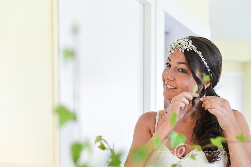 Novia arreglando el peinado en el espejo