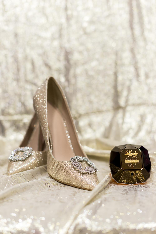 Zapatos de novia y perfume con fondo dorado