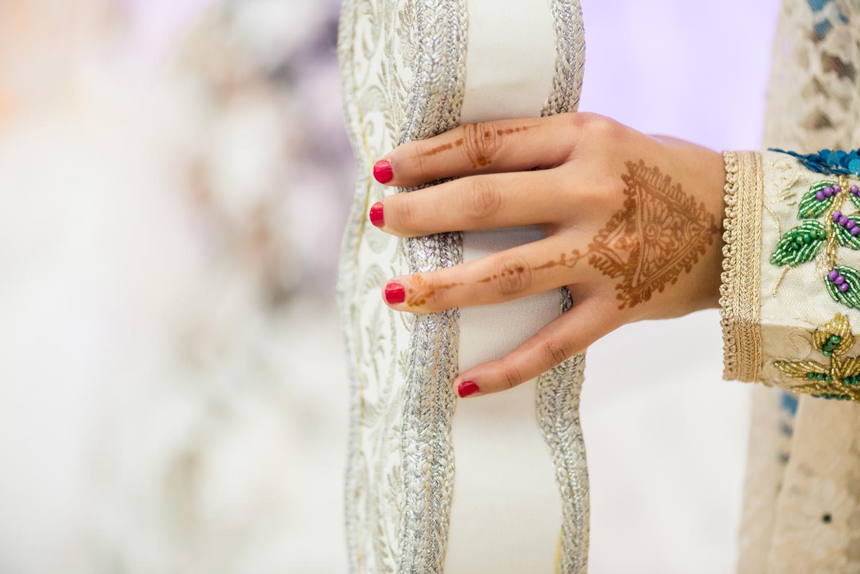 Henna en la mano con uñas rojas